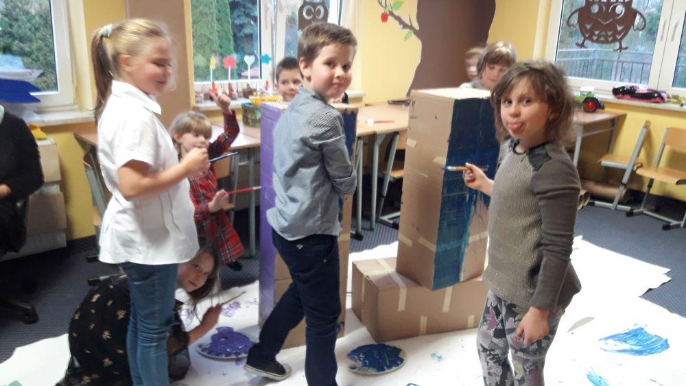 Uczniowie malują poszczególne części kredki - giganta