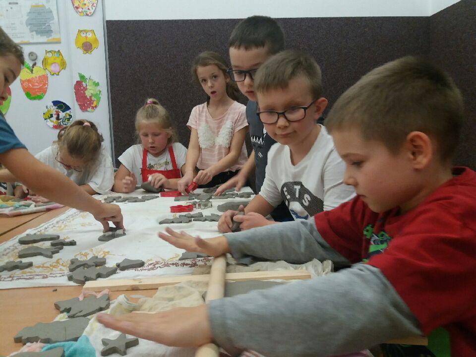 Dzieci wałkują glinę