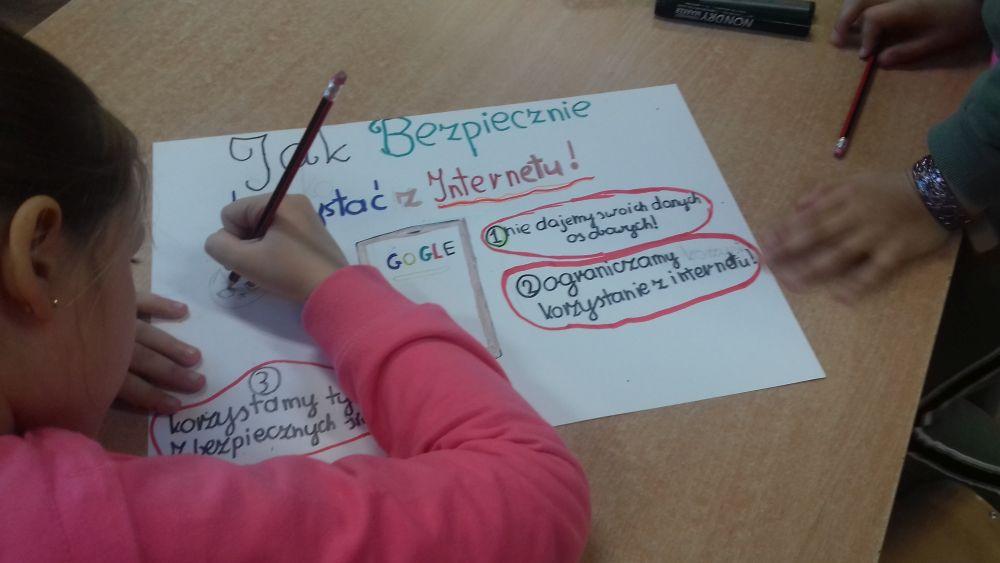 dziewczynka rysuje plakat o bezpieczeństwie w Internecie