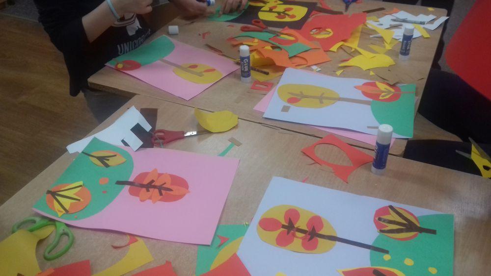 """dzieci wykonują pracę plastyczną z papieru kolorowego """" Jesienne drzewa"""""""