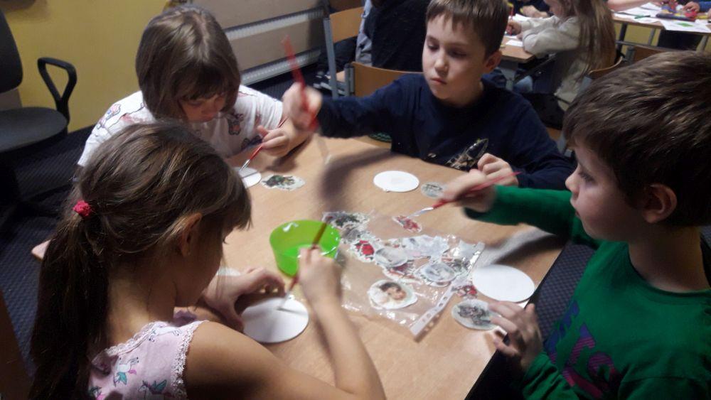 uczniowie rozprowadzają lakier na ozdobie choinkowej