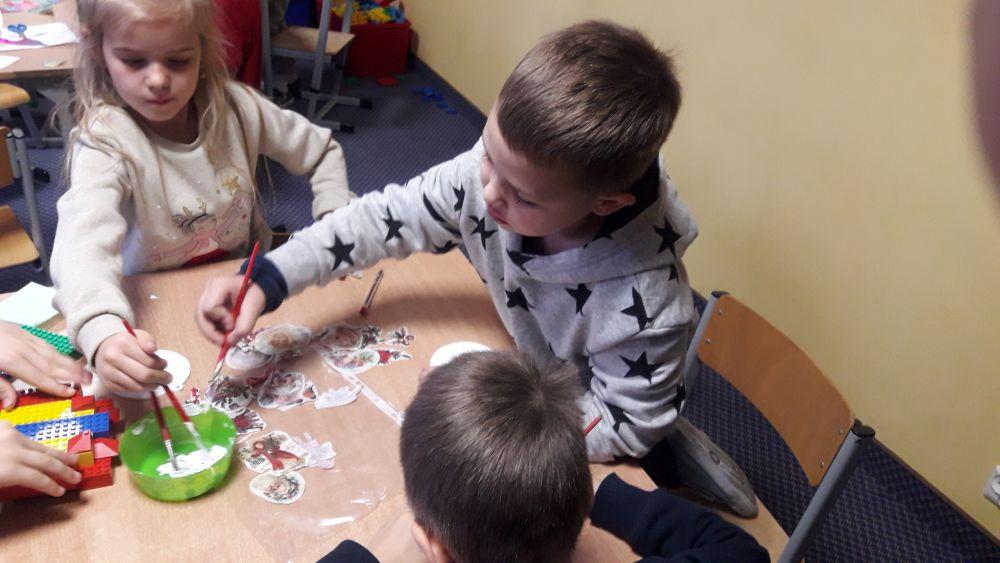 dzieci przyklejają obrazek z papieru ryżowego do drewnianej powierzchni bombki