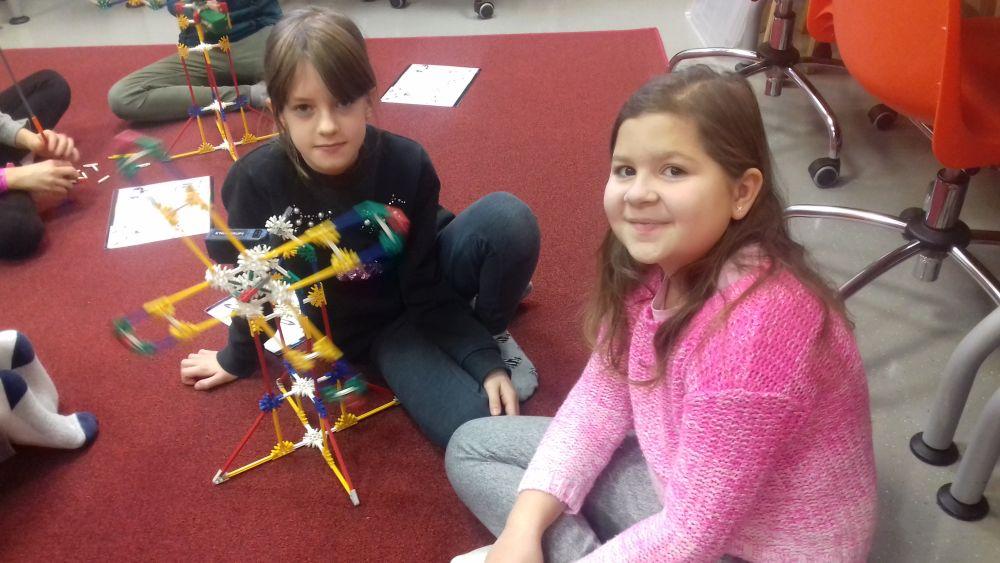 dziewczynki prezentują swoją budowlę z klocków K'Nex - wiatrak