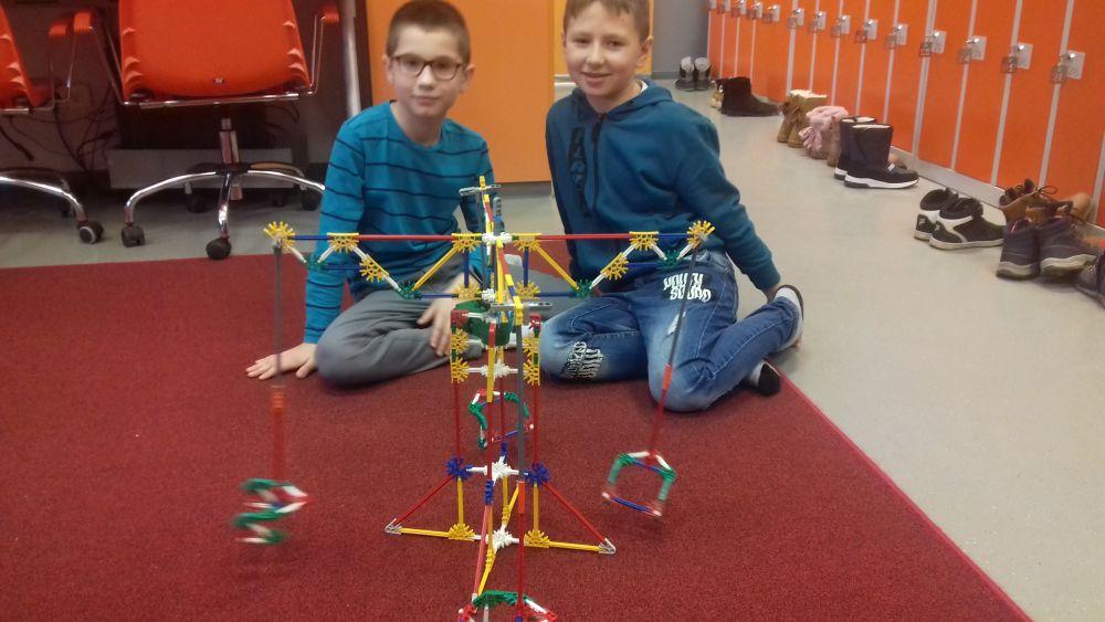 chłopcy prezentują swoją budowlę z klocków K'Nex – karuzela