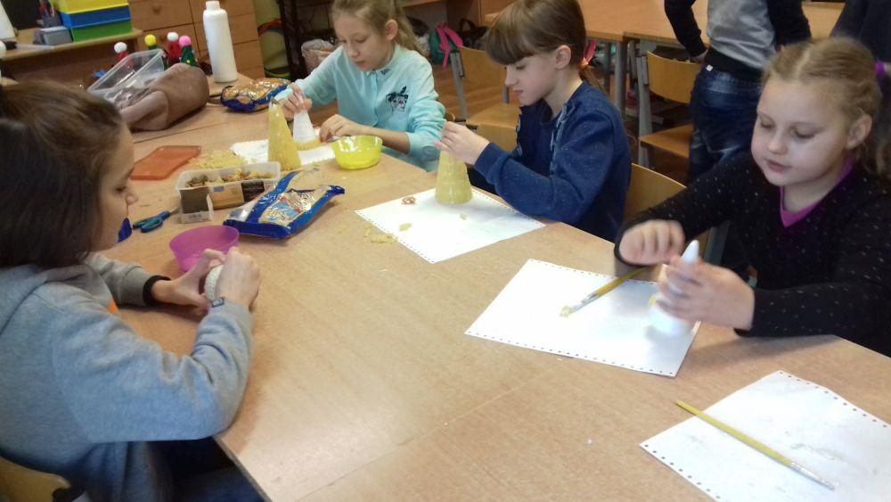 Dzieci oklejają stożki styropianowe makaronem