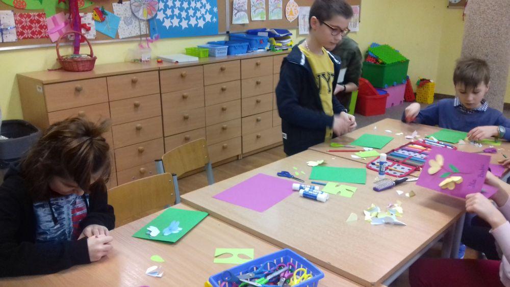 dzieci wykonują laurki z papieru kolorowego