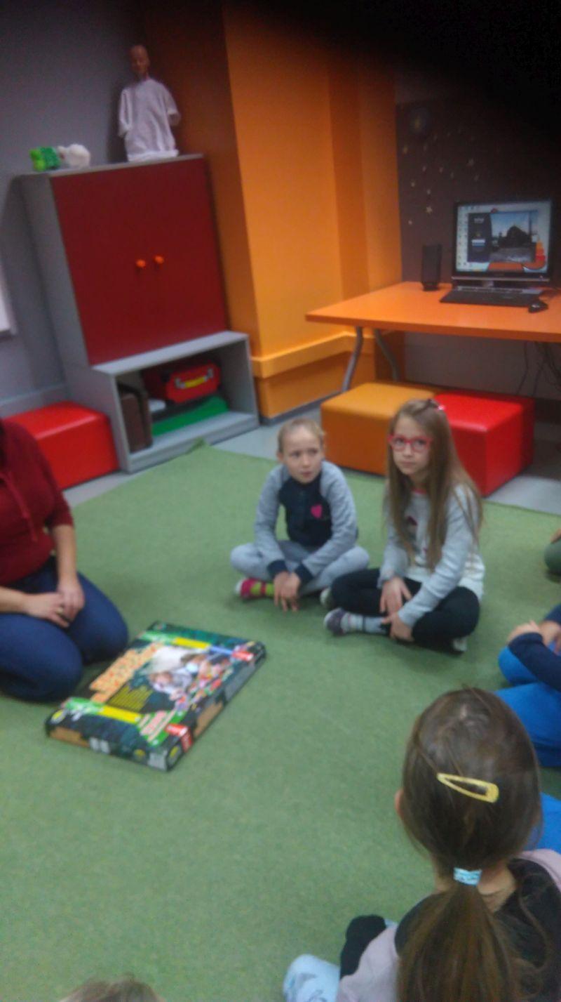 dzieci siedzą w kręgu i słuchają prowadzącego zajęcia