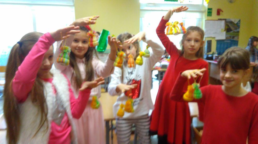 dzieci prezentują wykonane ozdoby – czapeczki z włóczki