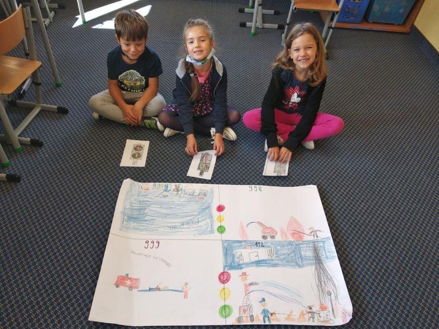 dzieci prezentują narysowany plakat z numerami alarmowymi