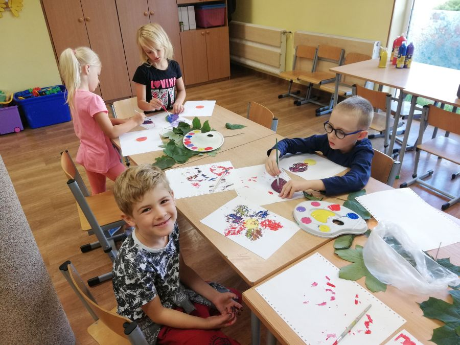 zdjęcie przedstawia dzieci wykonujące pracę plastyczną