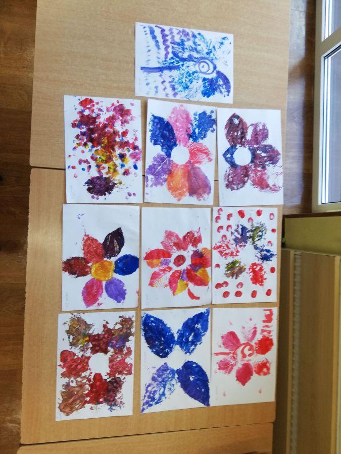 -zdjęcie przedstawia obrazy wykonane przez dzieci poprzez odbijanie pomalowanych farbą liści na papierze