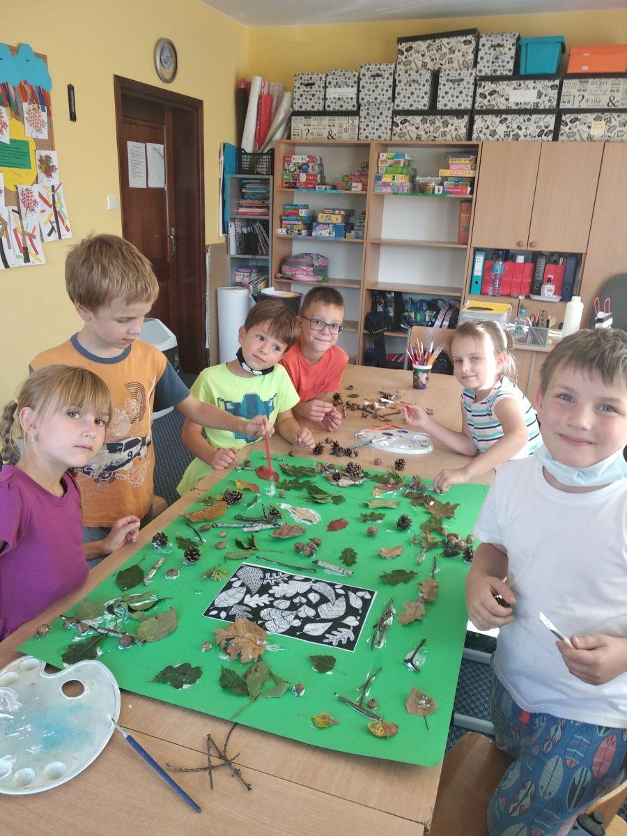 dzieci przyklejają liście, żołędzie i patyki na brystol