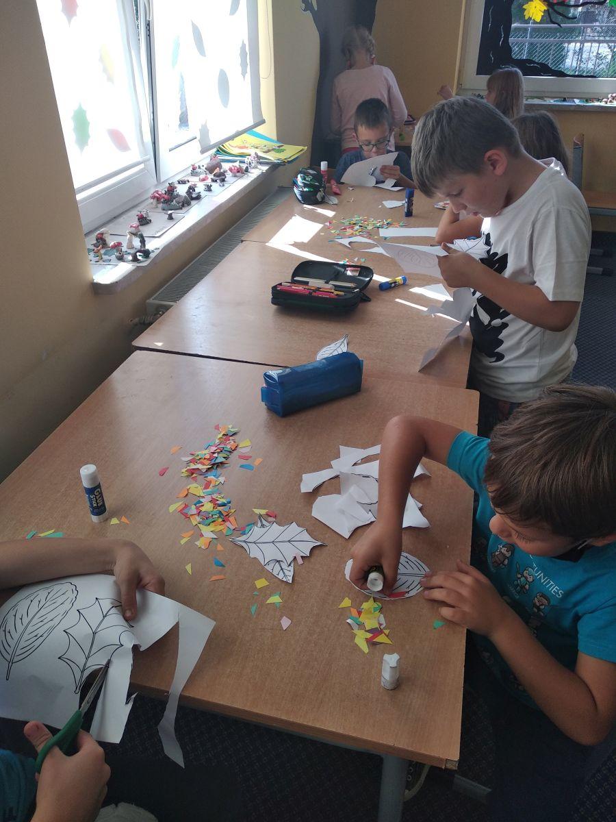 dzieci wycinają liście i przyklejają mozaikę