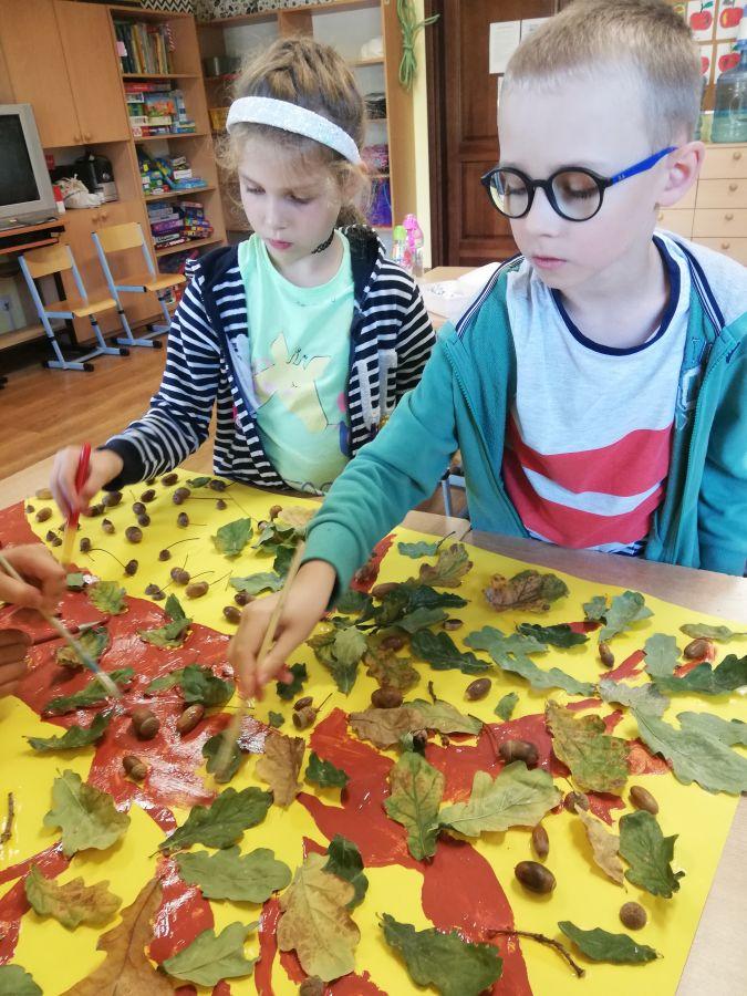 zdjęcie przedstawia dzieci malujące drzewo