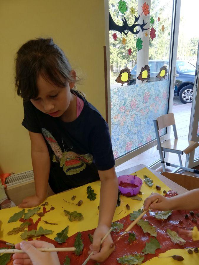 zdjęcie przedstawia dziewczynkę podczas wykonywania pracy plastycznej
