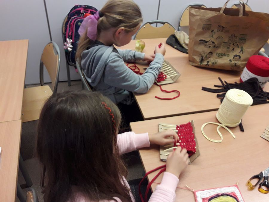 Uczennice z klas trzecich wyplatają dywaniki z bawełnianych sznurów