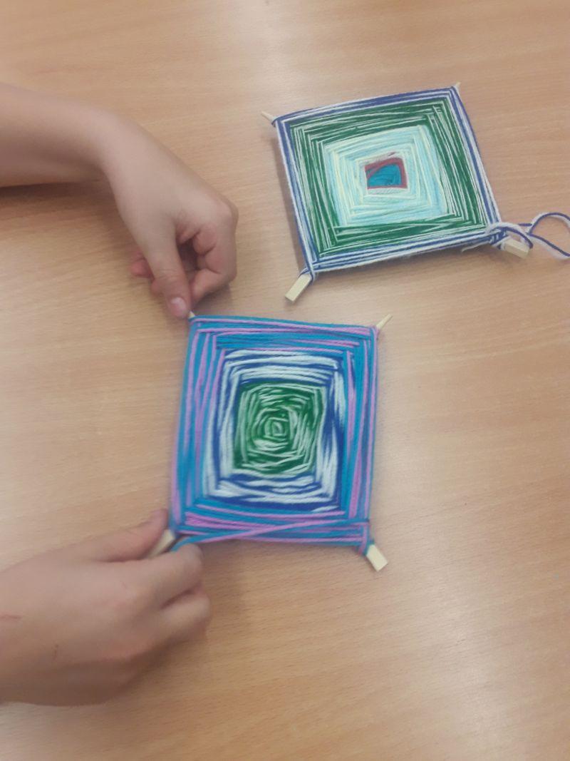 Uczeń klasy trzeciej pokazuje dwa dywaniki własnej produkcji