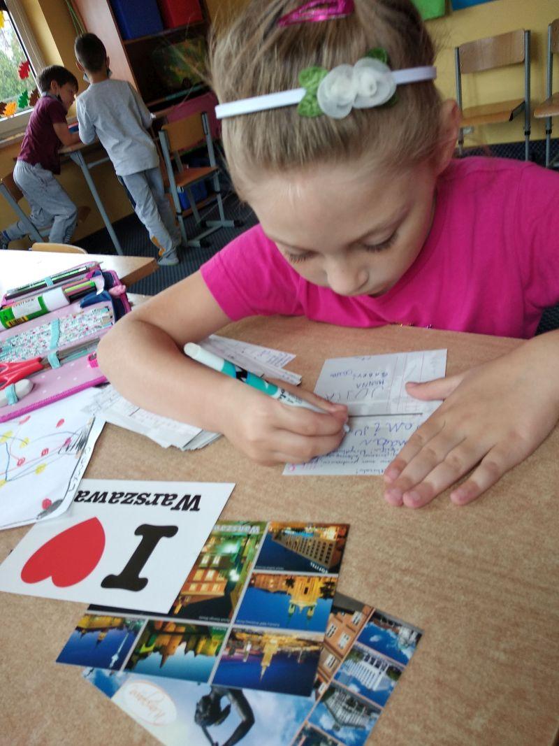 dziewczynka podpisuje sie na pocztówce