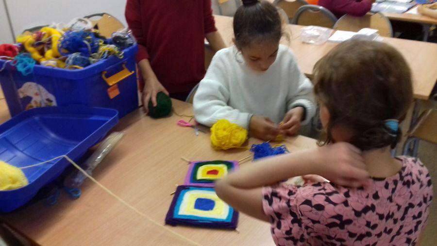 Dziewczynki robią dywaniki z włóczki i patyczków