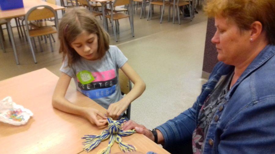 Dziewczynka wykonuje ośmiornicę z włóczki