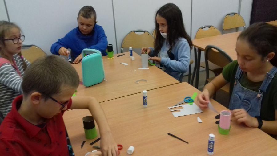 Dzieci wykonują zwierzątka z papieru kolorowego i rolek