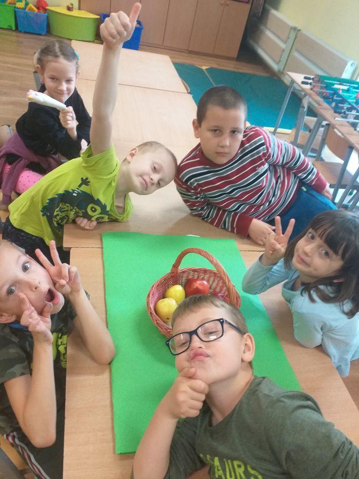 dzieci siedzą przy koszu jabłek