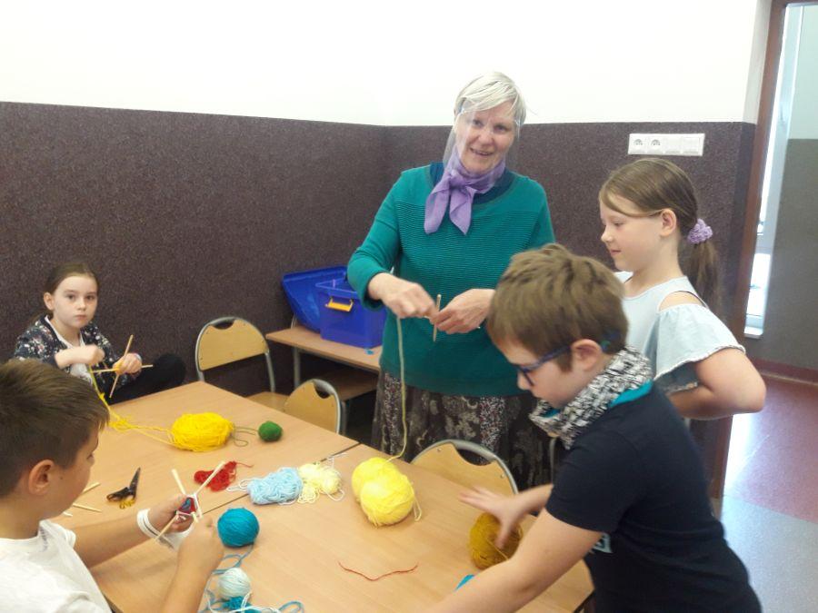 Wychowawca świetlicy opisuje dzieciom jak wykonać włóczkowe cudo
