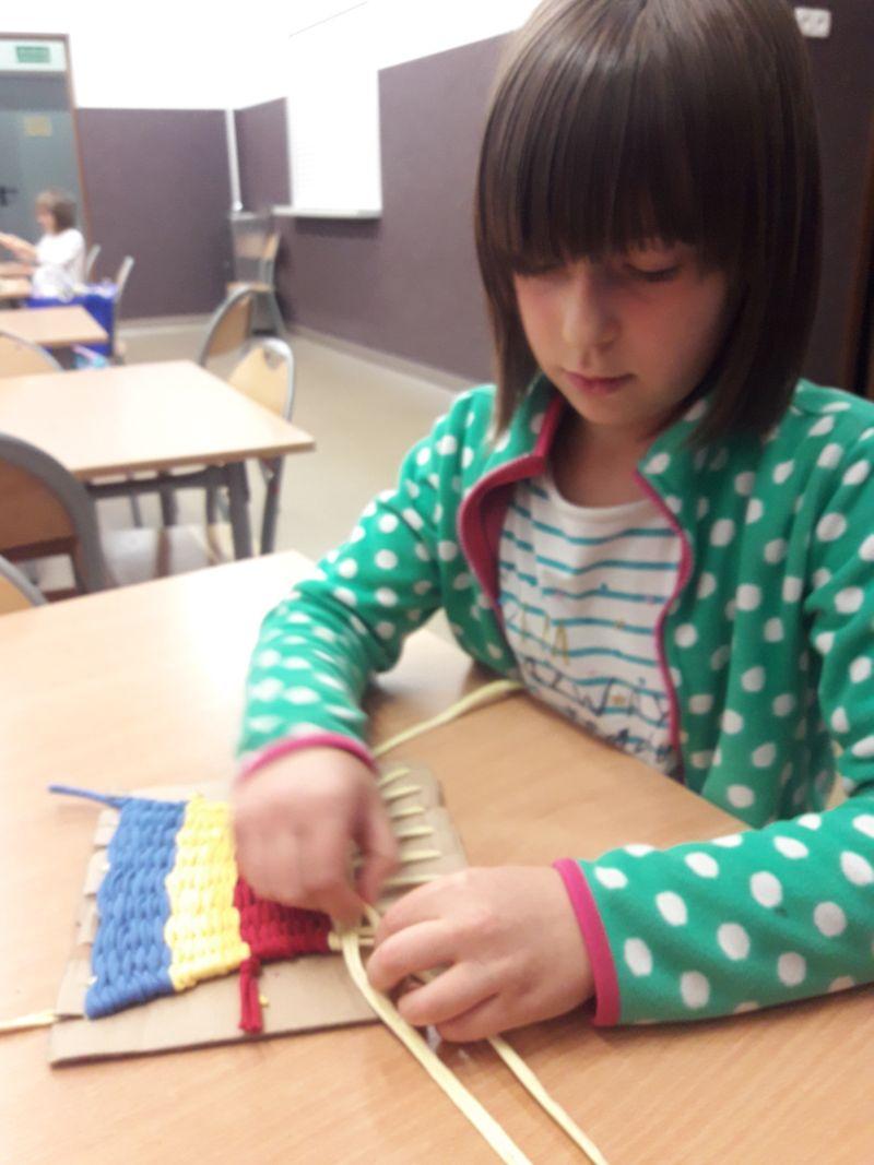 Uczennica klasy drugiej kończy wykonywać dywanik w trzech kolorach