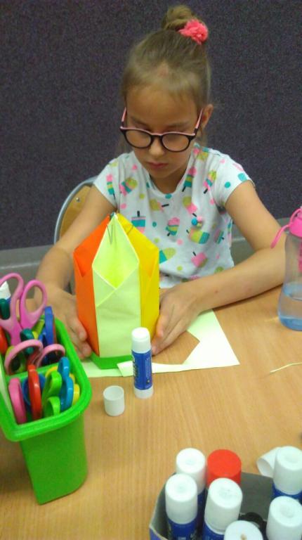 Dziewczynka konstruuje organizer z papieru kolorowego