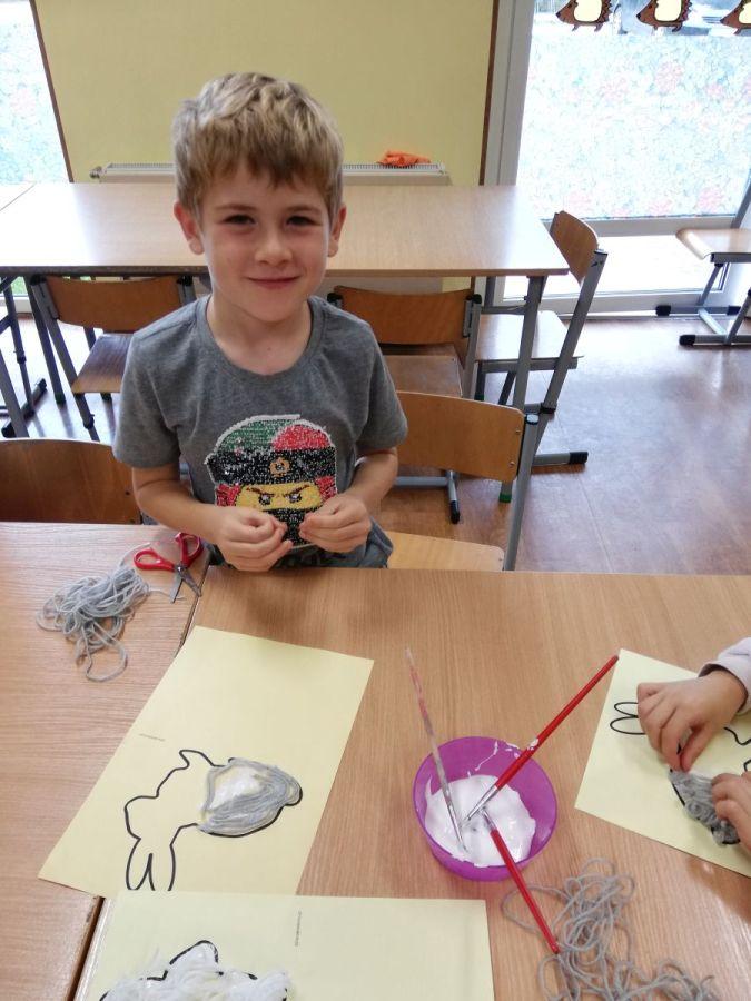 chłopiec wykonujący pracę plastyczną