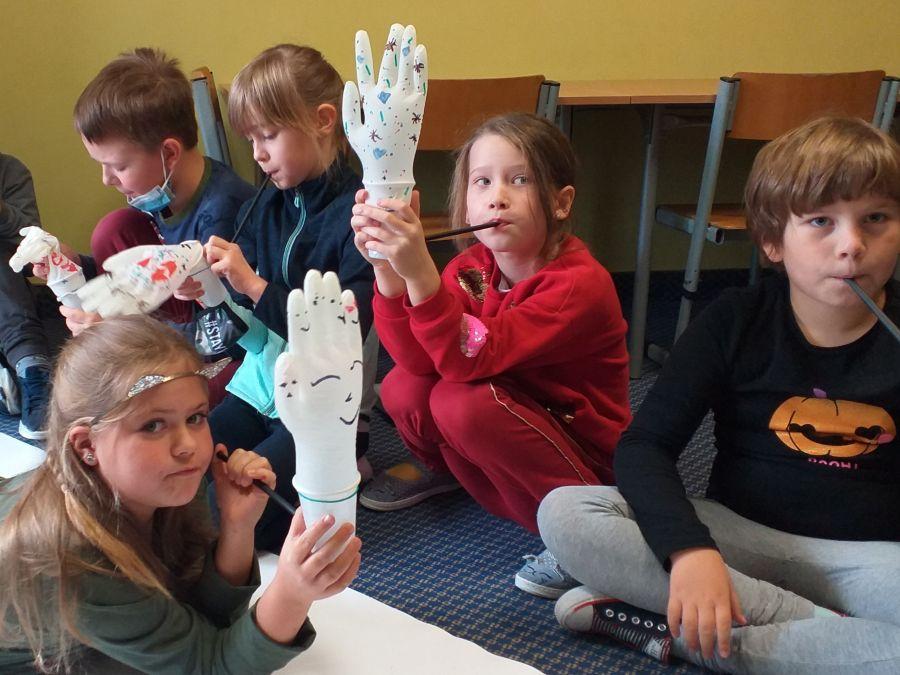 Dzieci wykonują zabawkę z rękawiczki, kubeczka i słomki