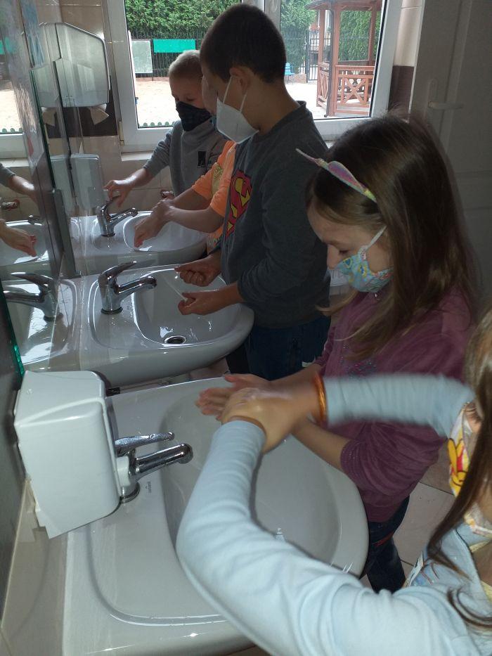 Dzieci zgodnie z instrukcją zawieszoną w łazience myją ręce