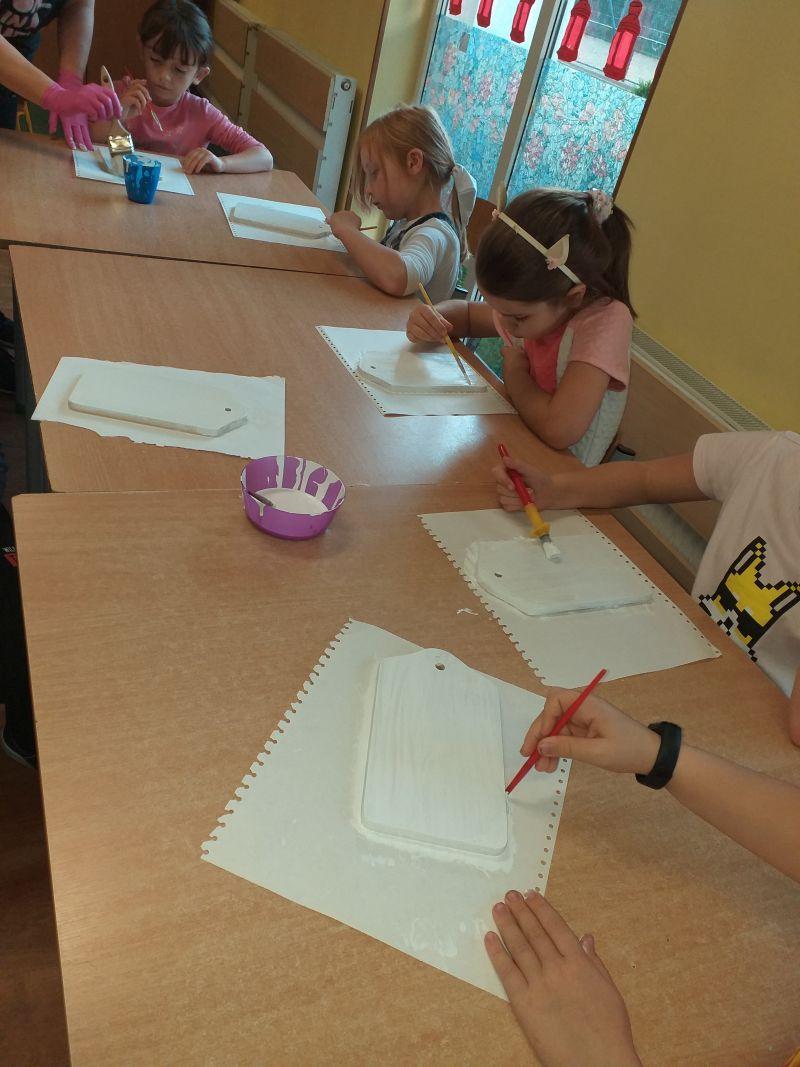 Dzieci malują farbą deseczki