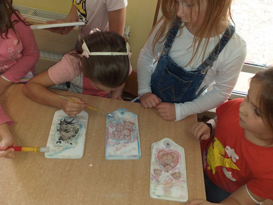 Dzieci naklejają serwetki na deseczki