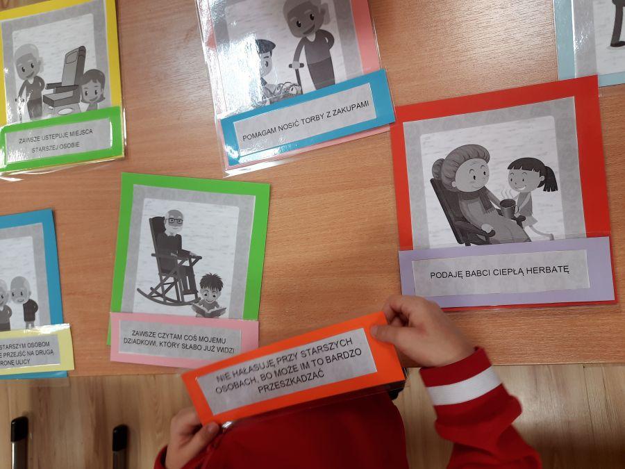 dzieci dopasowujące podpisy do Ilustracji przedstawiających pomoc starszym osobom