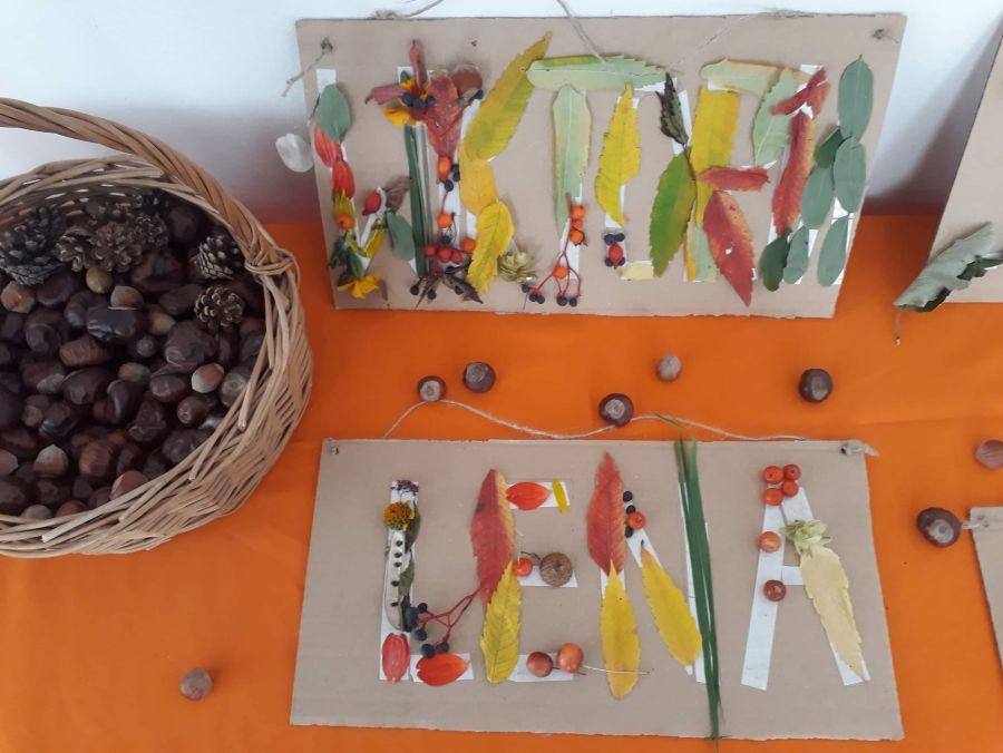 Prace wykonane przez dzieci -litery tworzące imiona dzieci ułożone z liści, patyczków jarzębiny oraz żołędzi przyklejone do tekturowej tabliczki.