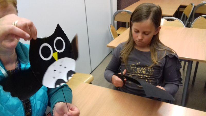 Pani prezentuje zabawkę ruchomą - sowę wykonaną z papieru kolorowego, dziewczynka wycina sowę z papieru