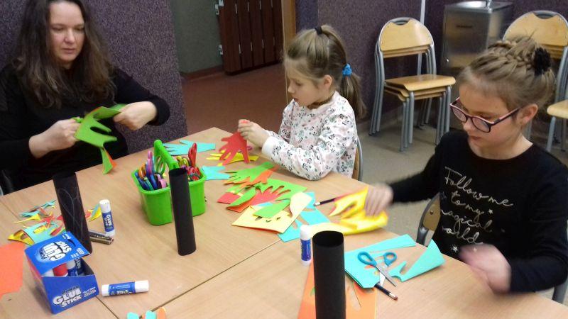 Pani i dwie dziewczynki wycinają liście w kształcie dłoni z papieru kolorowego