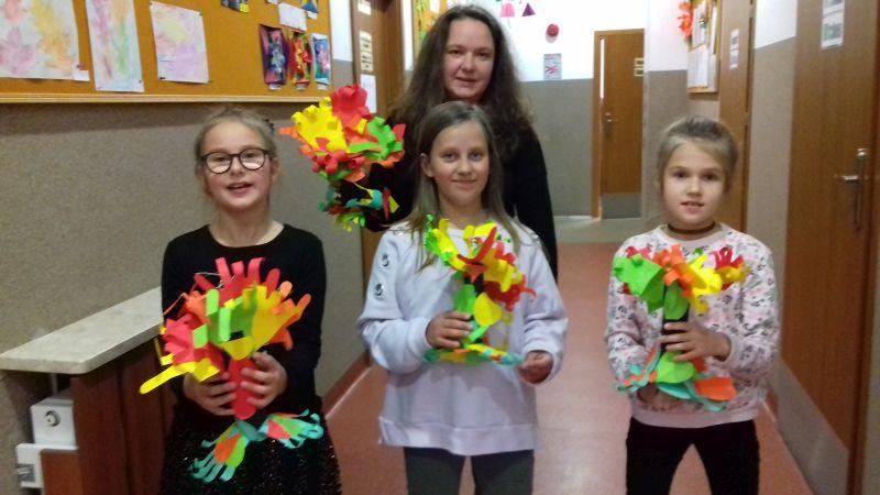 Pani i dziewczynki prezentują wykonane drzewa z papieru kolorowego i rolek