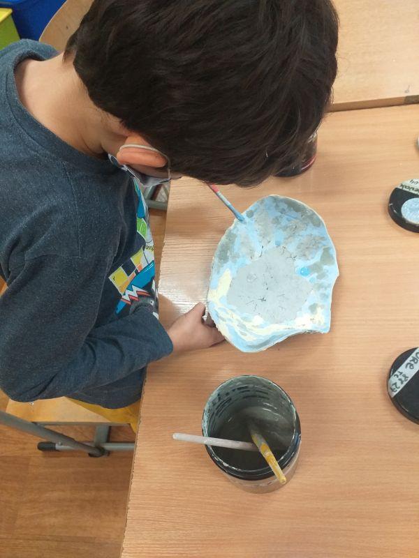 Dziecko pokrywa farbą naczynie gliniane