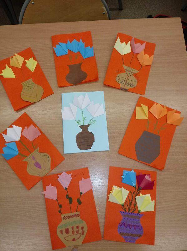 zdjęcie przedstawia laurki wykonane przez dzieci z kwiatami w wazonie z papieru kolorowego