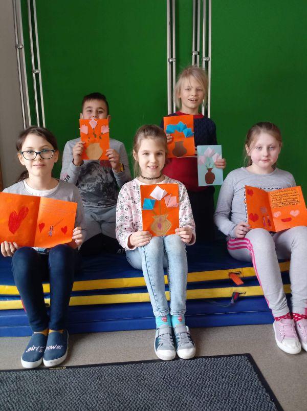 dzieci prezentują laurki w sali gimnastycznej siedząc na materacach