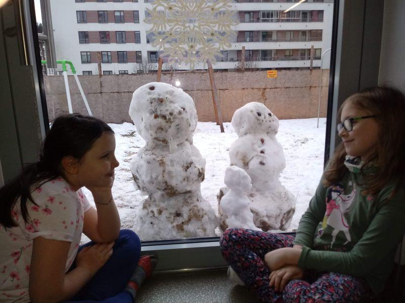 dziewczynki obserwują przez okno ulepione ze śniegu bałwany