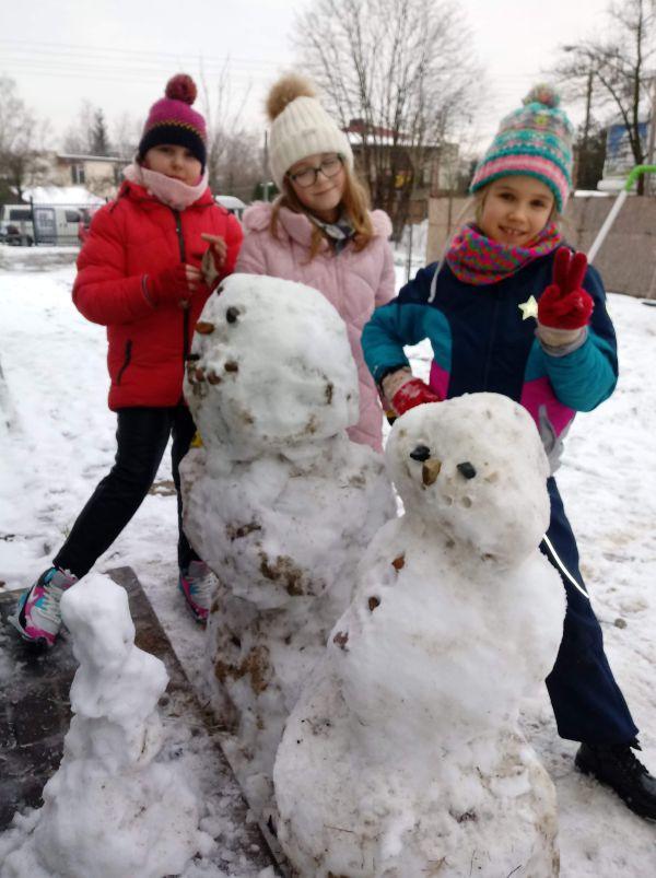 dzieci bawią się na śniegu, prezentują ulepione bałwany