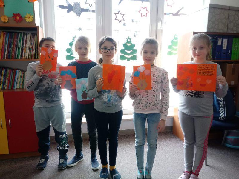 dzieci prezentują laurki w świetlicy stojąc