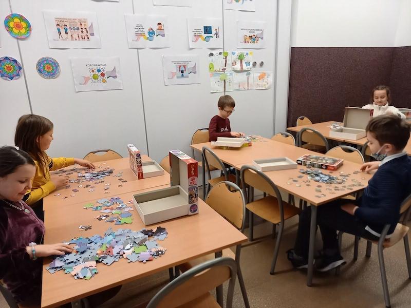 dzieci układają puzzle siedząc przy stolikach