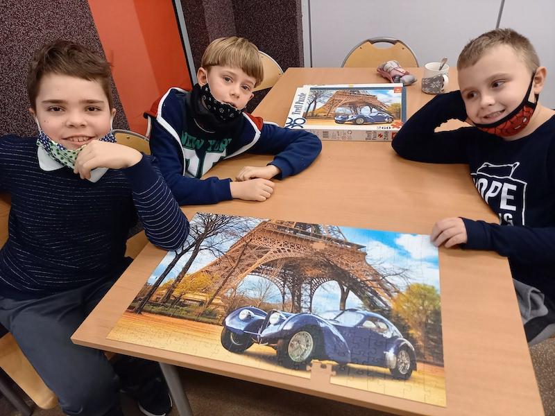 chłopcy prezentują ułożone przez siebie puzzle – samochód na tle wieży Eiffla