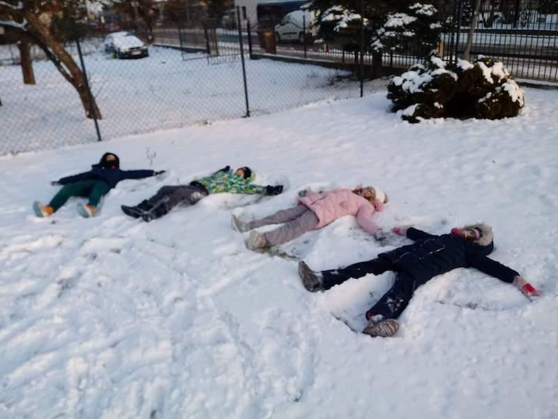 """dzieci tworzą """"aniołki"""" na śniegu"""