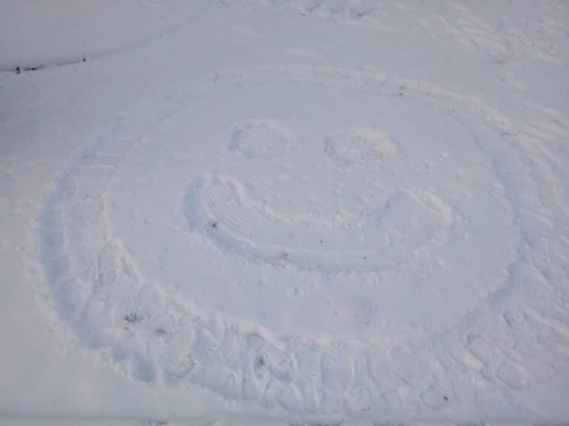 rysunek uśmiechu stworzony przez dzieci na śniegu