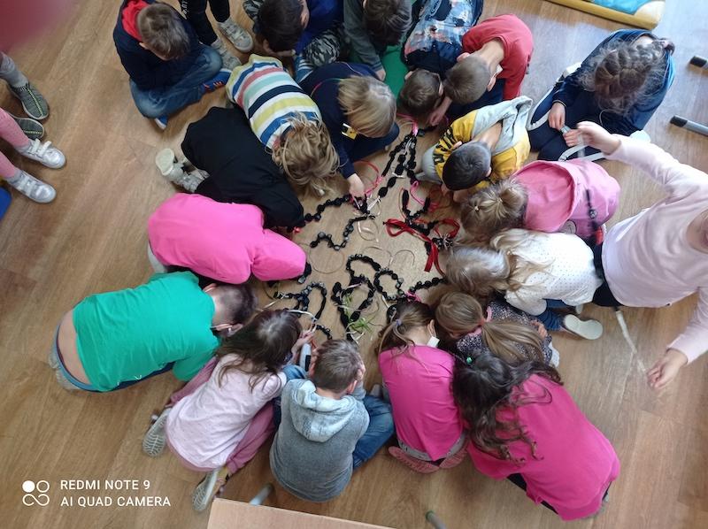 Uczniowie prezentują korale wykonane podczas zajęć.
